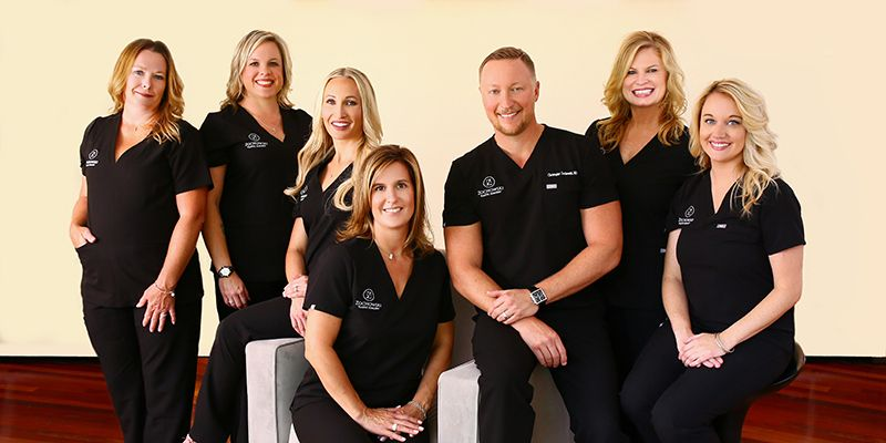 Dr. Zochowski and his plastic surgery staff in black medical scrubs