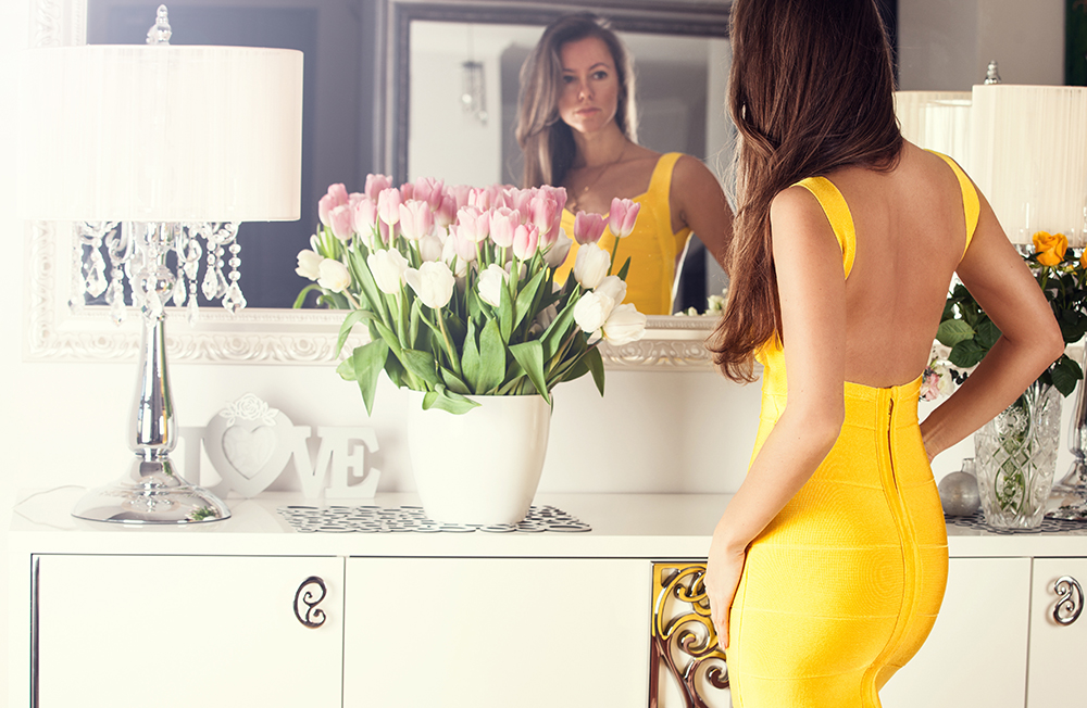 woman in slinky yellow dress looking at herself in mirror