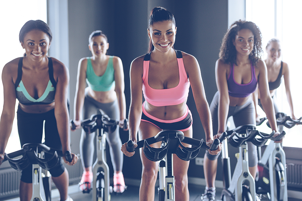 quintet of big-breasted young women in sports bras on stationary bicycles