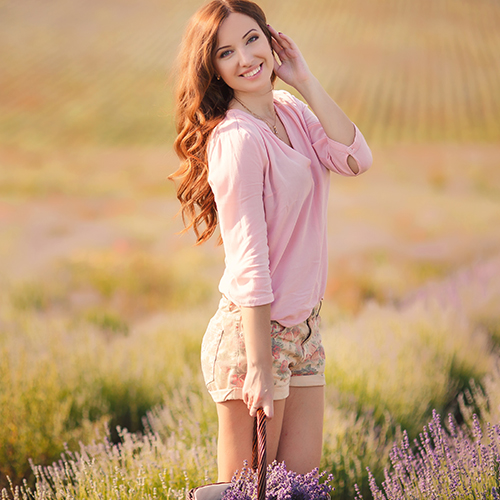young woman in pink shirt and floral shorts in lavender field