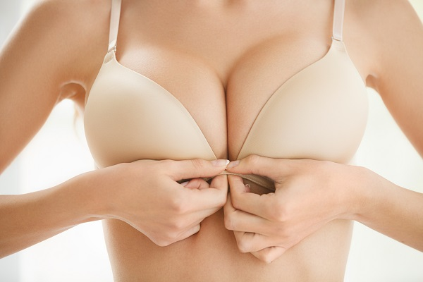 closeup of woman putting on bra
