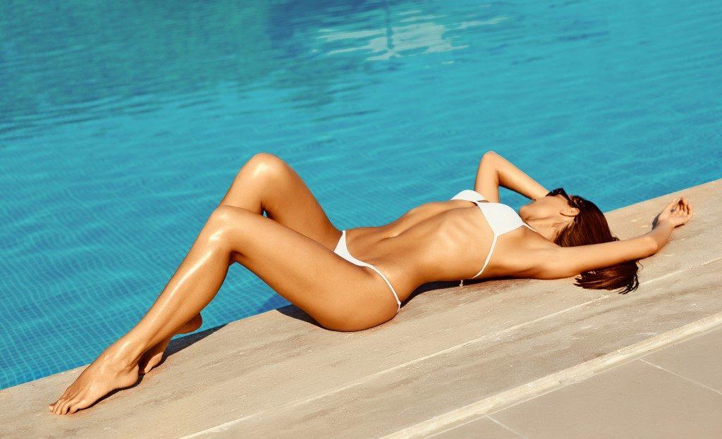slim woman in white bikini lying poolside
