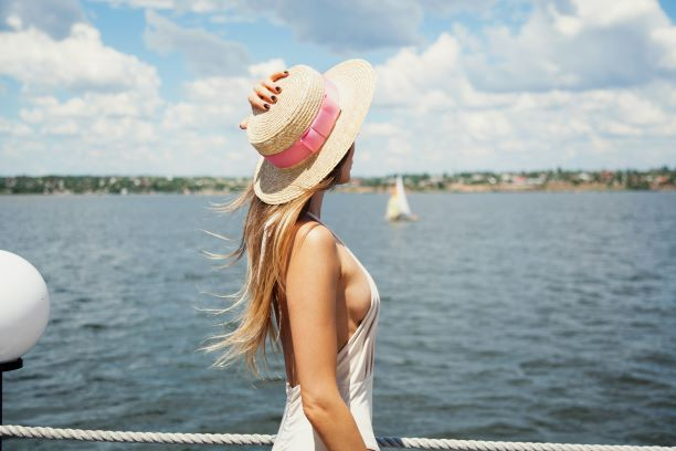 woman with small breasts in straw hat looking over the sea