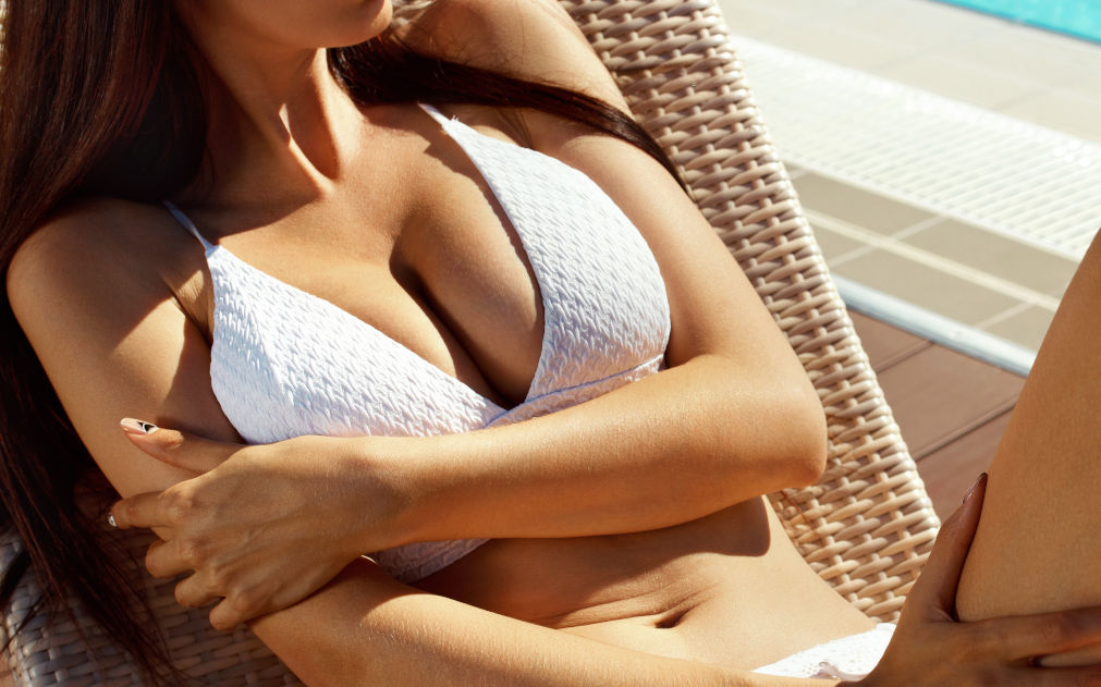 closeup of woman in white bikini on reclining lounge chair