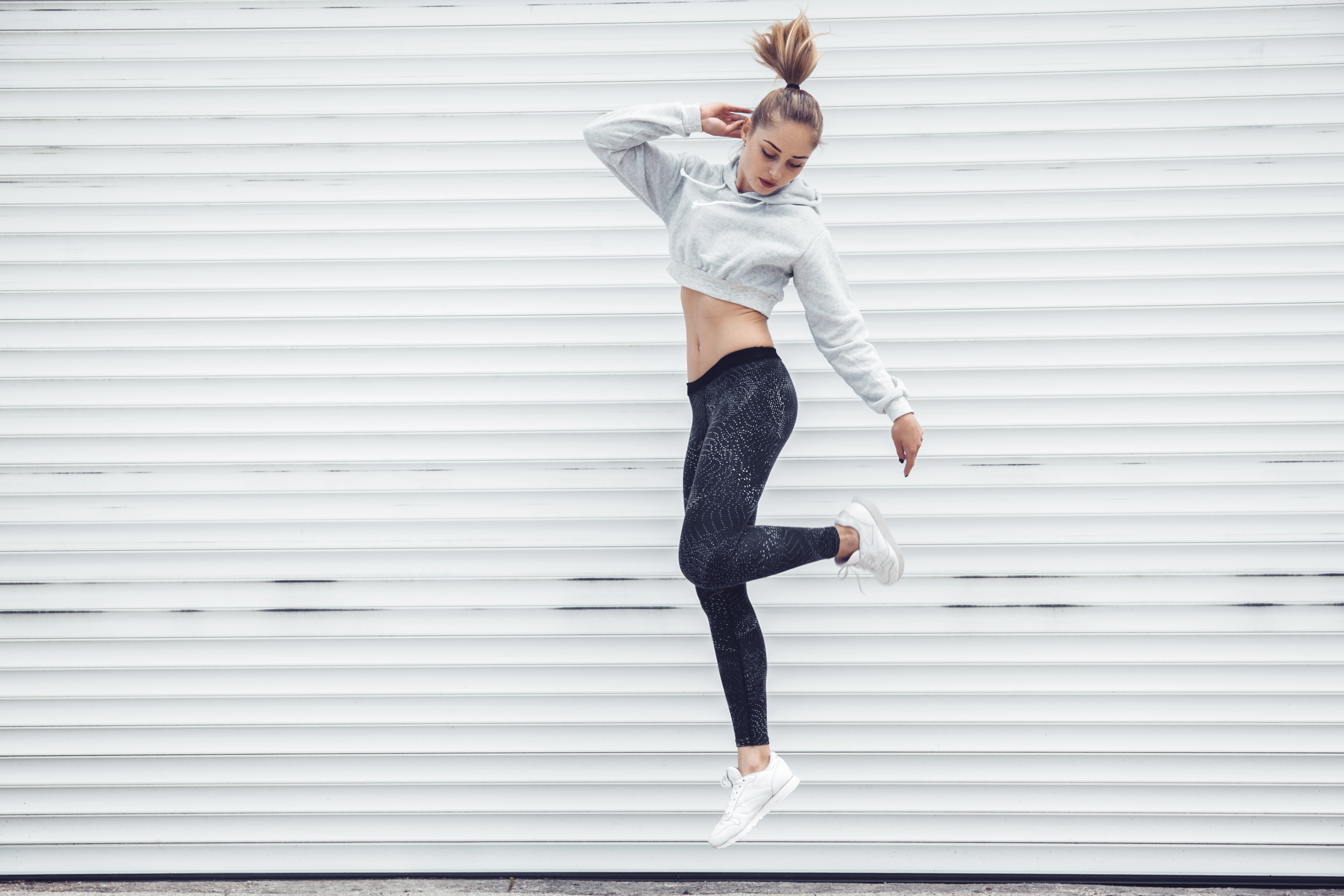 young woman in yoga pants and sweatshirt jumping