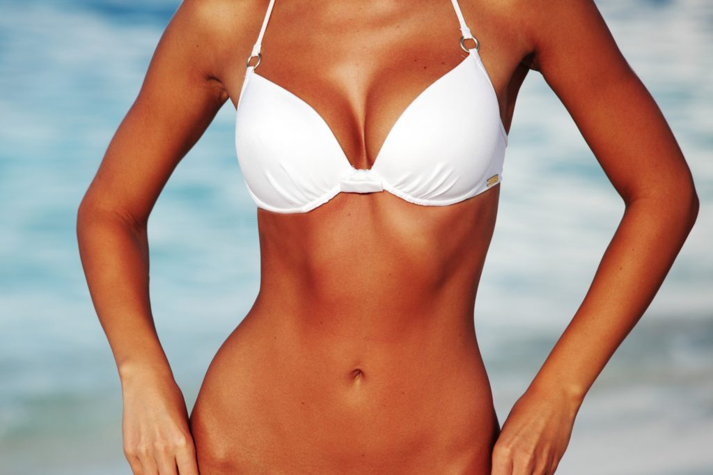 closeup of a woman's midsection in a white bikini