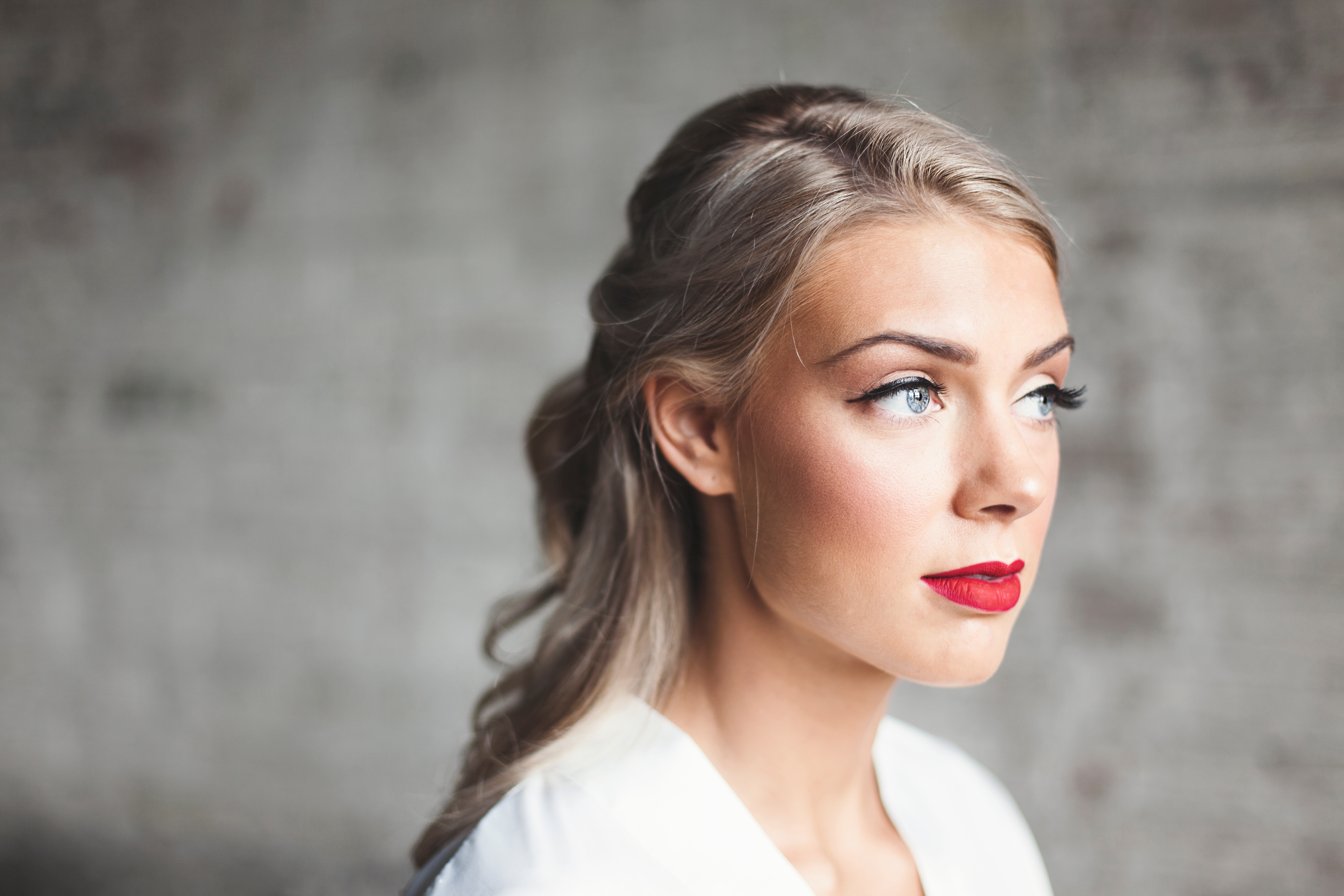 blue-eyed, blonde woman with smooth facial skin and red lipstick