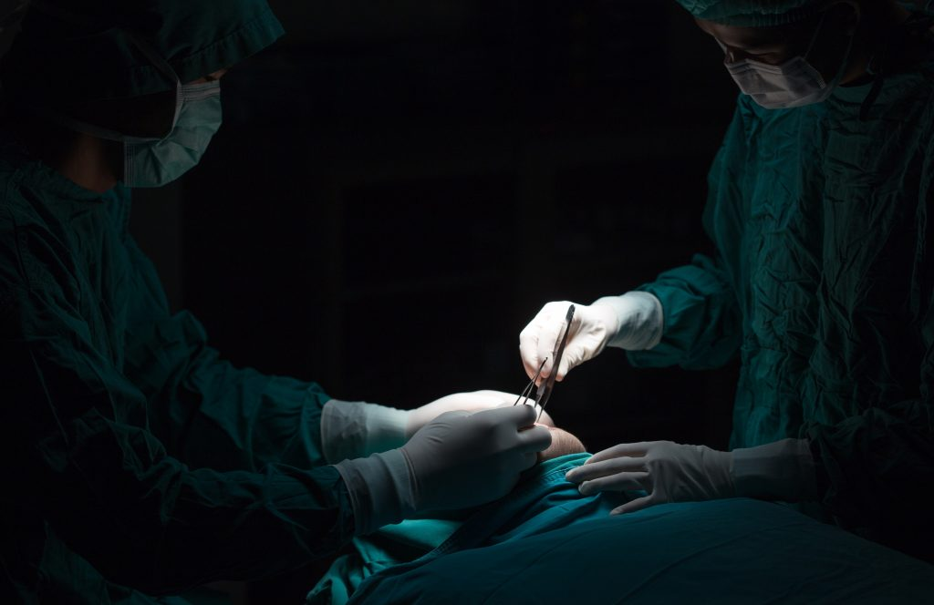 two medical providers in scrub suits operating on a patient
