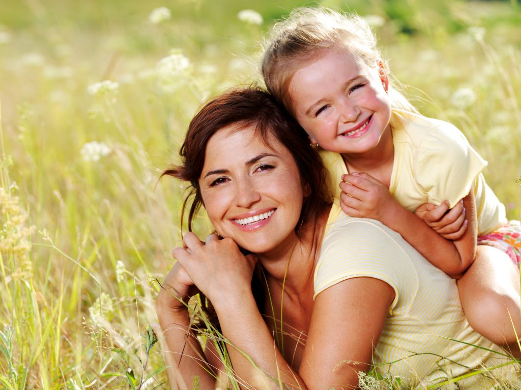 female child on mother's back in a grassy field